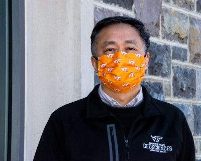 Xiao poses with orange Virginia Tech mask, and Geosciences jacket outside a Hokie Stone building.