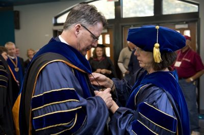 Timothy and Laura P. Sands help each other adjust their University of California, Berkeley, regalia before joining the processional.